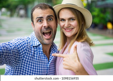 Happy middle-aged couple posing, taking selfie photo outdoors