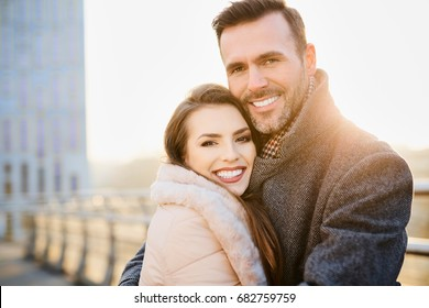 Happy middle-aged couple smiling and looking at camera while hugging each other
