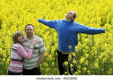 Happy middle-aged couple and their son in flower meadow.