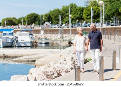Happy middle-aged couple walking hand in hand past a small boat marina at the coast as they enjoy an active day in the summer sun