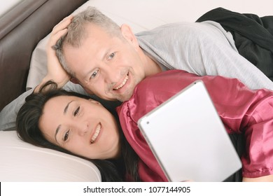 Happy middle-aged couple watching video on tablet at home. Indoors