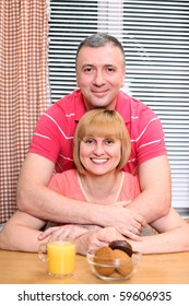 A happy middle-aged loving couple having cuddles during meal in the kitchen