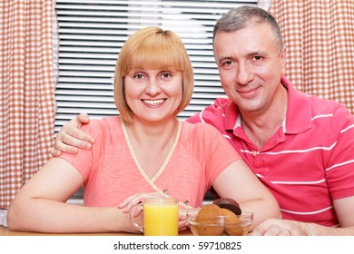 A happy middle-aged loving couple having meal in the kitchen. Focus on wife.