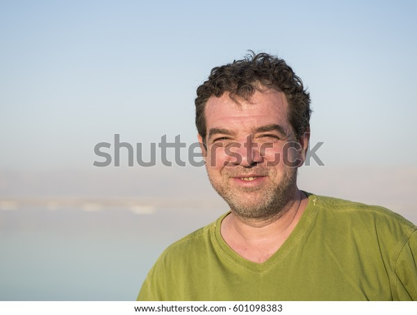 Happy middle-aged man in green t-shirt on sea landscape background