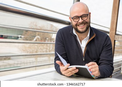 Happy middle-aged man making notes in street cafe. Bold man wearing casual clothes, looking at camera and sitting at table in outdoor cafe. Planning concept. Front view.