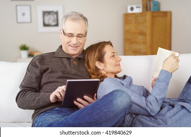 Happy middle-aged married couple relaxing together at home with the wife lying back against her husband as she reads a book while he surfs the internet on a tablet