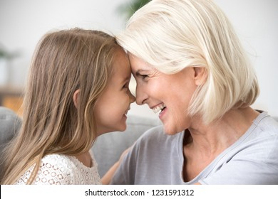 Happy middle-aged mature grandma and little preschool granddaughter touching noses laughing together, smiling loving old grandmother granny and cute carefree grandkid girl having fun playing at home