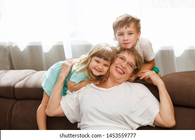 Happy middle-aged mature grandma and  little preschooler two grandsons having fun playing at home