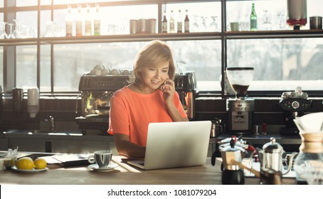 Happy middle-aged woman barista working on laptop and talking on smartphone, accepting an order at modern coffee shop. Small business, online purchase and service concept, copy space