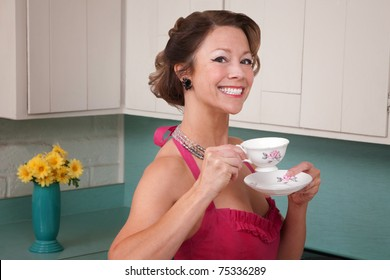 Happy middle-aged woman drinking coffee in kitchen