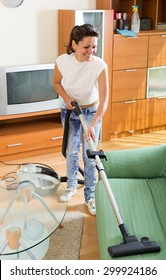 Happy middle-aged woman hoovering apartment