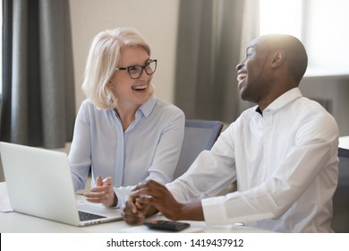 Happy middle-aged woman and millennial african American man sit at office desk work on laptop together laughing on funny joke, smiling diverse colleagues have fun talking cooperating at workplace