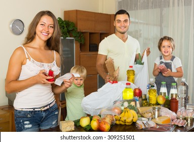 Happy middle-class family of four with bags of food at home