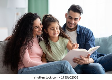 Happy Middle-Eastern Family With Little Daughter Reading Book Together