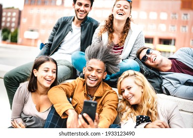 Happy milenial people having fun sharing photo on mobile phone after lockdown reopening - Joyful concept about guys and girls spending time together outdoor at university college - Warm bright filter