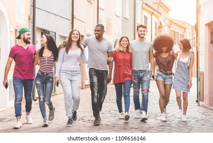 Happy milennials friends walking in old town city centre - Young people having fun together - Youth lifestyle and friendship concept - Focus on center guys