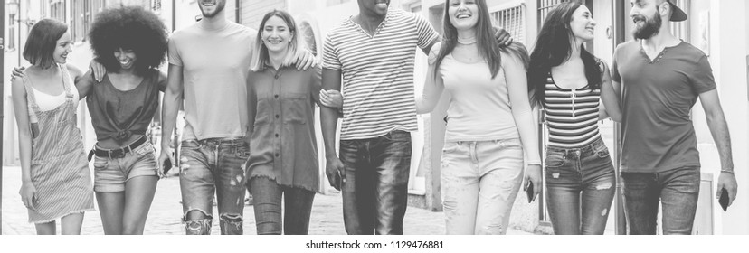 Happy milennials friends walking in urban down town - Young people having fun together - Youth lifestyle and friendship concept - Focus on center guys  - Black and white editing