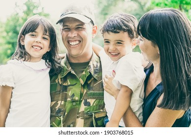 Happy military man posing for camera with his family, holding kids in arms, his wife hugging all of them and laughing. Medium shot. Family reunion or returning home concept