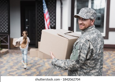 Happy military serviceman holding cardboard box and looking at camera with blurred girl on background