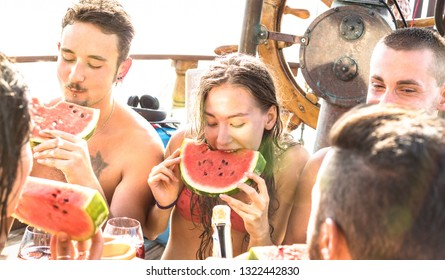 Happy millenial friends having fun at sail boat party with watermelon sangria and champagne - Cool friendship concept with young multi racial people on sailboat - Exclusive and luxury travel lifestyle