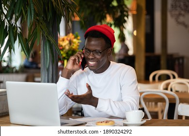 Happy millennial Afro-American hipster man wear red hat laughing, speaking with friend on mobile phone, enjoying watching educational webinar on laptop, remotely online work in cafe during lunchtime