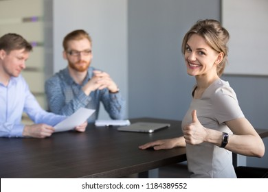 Happy millennial applicant showing thumbs up, successful woman vacancy candidate smiling feeling excited by win getting hired concept, portrait of female job interview winner looking at camera