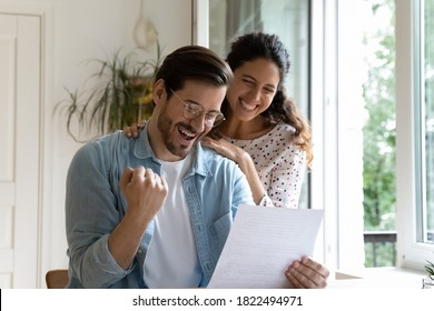 Happy millennial Caucasian couple feel excited euphoric reading amazing pleasant news in paper letter correspondence. Overjoyed man and woman get positive bank response in post paperwork or agreement.
