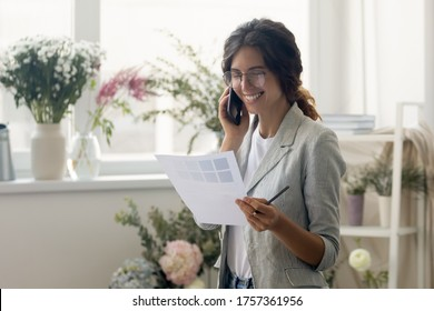 Happy millennial Caucasian female designer in glasses talk on smartphone with client discuss paperwork together, smiling businesswoman analyze paper document template with customer on cellphone call