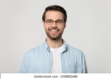 Happy millennial Caucasian guy wear glasses isolated on grey studio background smiling with white healthy teeth, positive young man in casual clothes posing look at camera show good treatment result