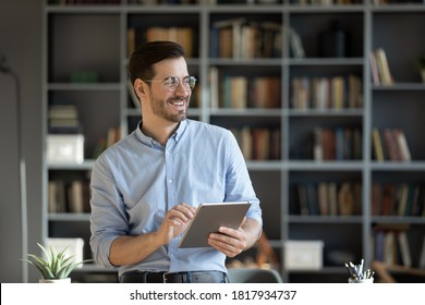 Happy millennial Caucasian man in glasses use tablet look in distance planning or visualizing future success. Smiling young male work on pad gadget, dreaming or thinking. Business vision concept.