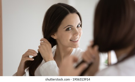 Happy millennial Caucasian woman look in mirror satisfied with healthy thick hair after salon treatment or restoration mask. Smiling young female do hairstyle show beauty cosmetic product results.