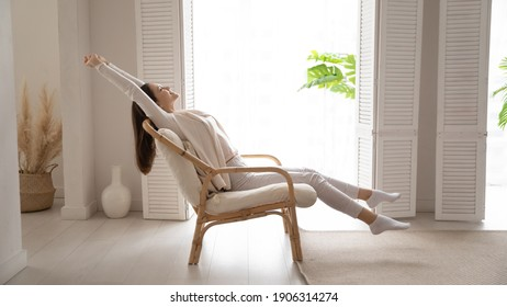 Happy millennial Caucasian woman sit in cozy chair in design home stretch relax breathe fresh air. Smiling young female renter or tenant rest in armchair relieve negative emotions enjoying weekend. - Shutterstock ID 1906314274