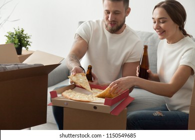 Happy millennial couple eating pizza and drinking beer on cardboard boxes celebrating moving in to new apartment, husband and wife having fun together on housewarming party, enjoying takeaway snacks