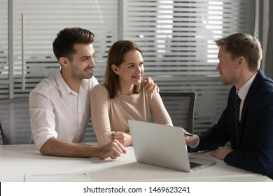 Happy millennial couple talk with male real estate agent or broker in office buying first house together, smiling young husband and wife speak visit banker think of taking loan or mortgage from bank