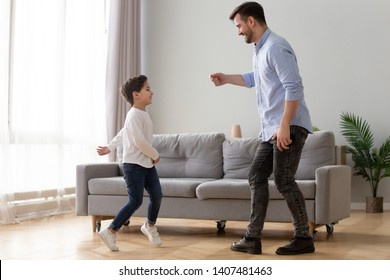 Happy millennial father and preschooler son have fun dancing together entertaining in living room, excited young dad and little boy child enjoy family leisure activity, jump relax at home on weekend