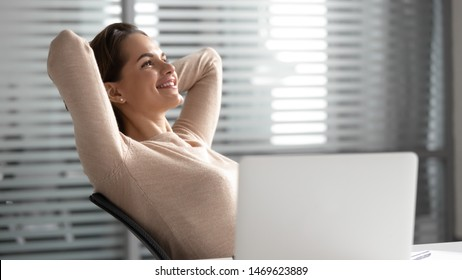 Happy millennial female employee relax in chair hands over head distracted from job visualizing, smiling dreamy woman rest at workplace satisfied with work finished, dreaming of career opportunities