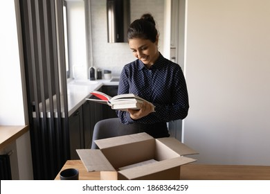 Happy millennial female of indian ethnicity preparing moving relocation to new home packing things. Glad proud young hindu woman author get parcel with personal copies of book from publishing house