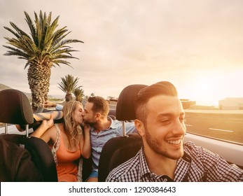Happy millennial friends having fun in convertible car at sunset - Young people driving and laughing together in summer vacation - Youth lifestyle and holiday concept - Main focus on right man face
