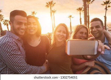 Happy millennial friends making a selfie story photo for social network app on summer vacation - Young people having fun with new trend technology - Travel and tech concept - Focus on center girl face