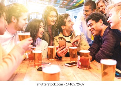 Happy millennial friends at pub drinking beer - Group of multiracial people having fun together at pub and looking at smartphone - Birthday party or after work meeting, happiness and teamwork concepts