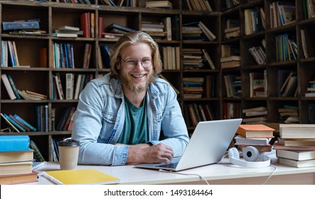 Happy millennial guy university student study online in library e learning easy internet course in app on laptop computer books at camera sit at desk, smiling young man teacher wear glasses, portrait