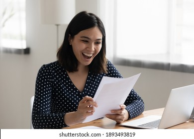 Happy millennial korean asian woman reading paper university admission notification, feeling excited alone at home. Euphoric smiling young mixed race female worker getting job promotion letter.
