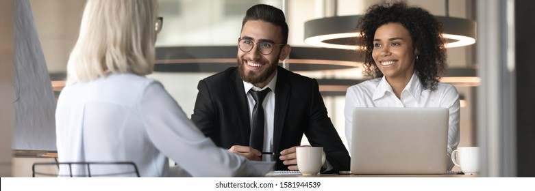 Happy millennial multiethnic recruiters talk with female job applicant at interview, woman work candidate make good first impression on smiling multiracial employers at recruitment meeting