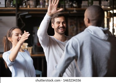 Happy millennial multiracial friends give hug meeting in bar reunited at friendly gathering, overjoyed diverse young people embrace welcome pal at party in cafe or restaurant. Friendship concept