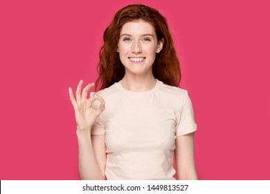 Happy millennial red-haired woman looking at camera, showing ok gesture, isolated on bright pink studio background. Smiling female customer agree with good deal, young employee accepting job offer.