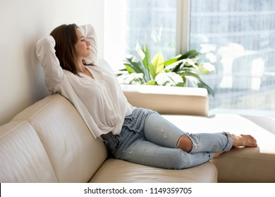 Happy millennial woman relaxing and stretching on cozy leather sofa during day off at home
