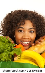 Happy millennial woman smiling with groceries around her face