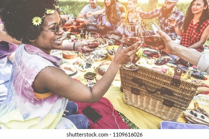 Happy millennials friends drinking and eating at picninc dinner outdoor - Young people having fun doing meal in nature - Friendship, youth lifestyle and summer concept - Focus on afro girl
