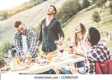 Happy millennials friends drinking wine and eating appetizer at bbq dinner in nature - Adult people having fun at meal in nature - Friendship and summer meal concept - Main focus on left man face