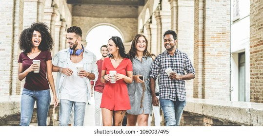 Happy millennials friends having fun together - Young students drinking coffee and laughing together in old town street- Youth lifestyle, school and friendship concept - Main focus on center hands